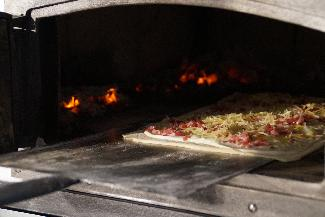 Traditional tarte flambée in wood-fire oven